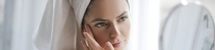 Woman after shower examining skin in the mirror and wondering shy her skin is darker than before