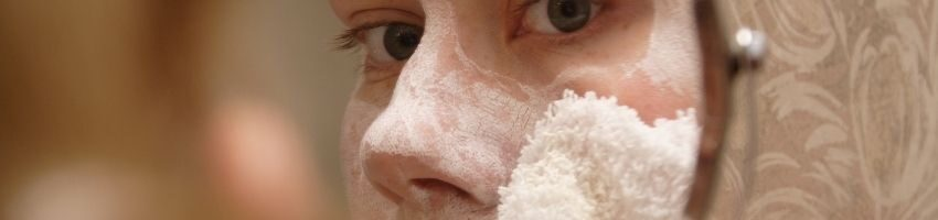 A woman applying acne moisturizer to her face