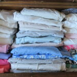 Folding clothes and storing vertically saves space.