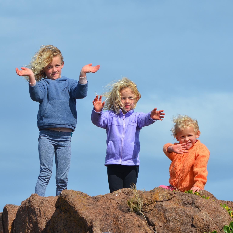 Canva - 3 Kids Standing on Rock
