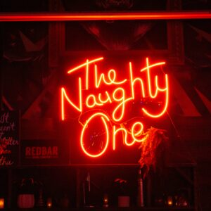 This is an Image of The Naughty One neon sign hanging in RedBar Brickell.