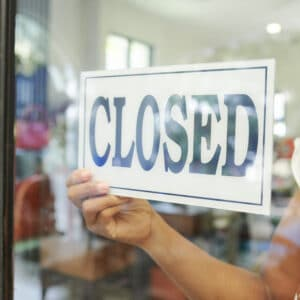 Close-up of saleswoman hanging the Closed sign on glass door and closed the store
