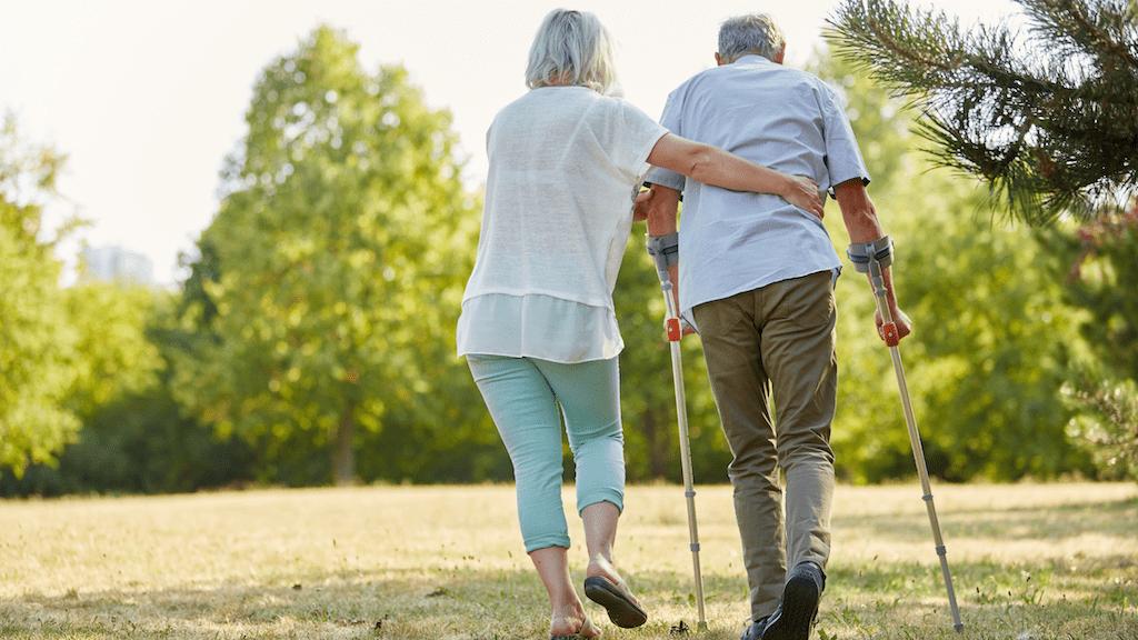 Home care worker helping elderly man walk in field.