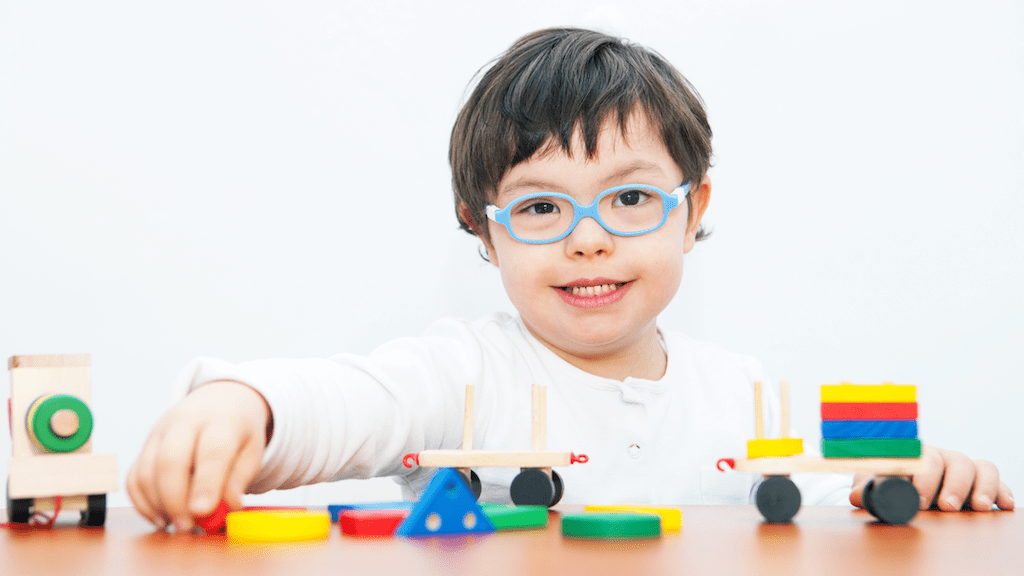 Young child playing with blocks and toys; respite care for children with disabilities.