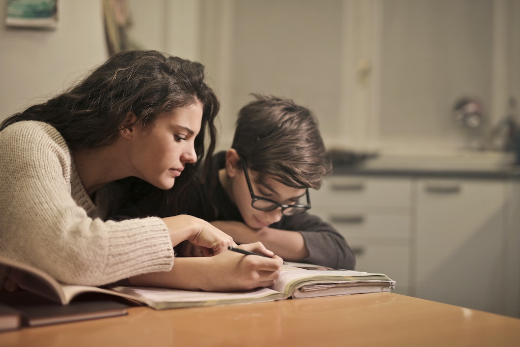 Home care worker helping child with ADHD do homework