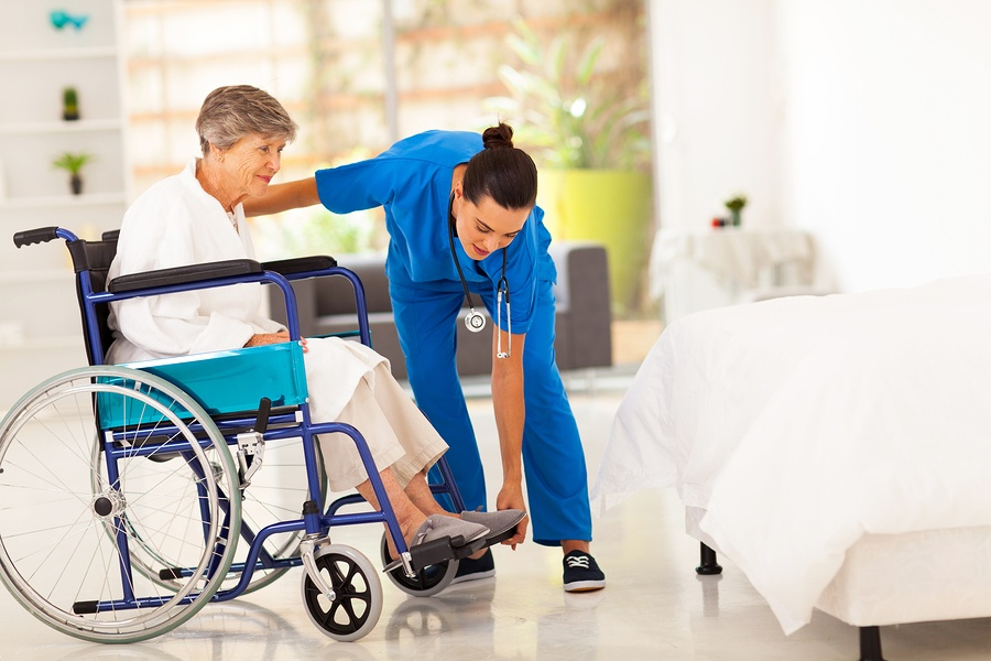 caregiver helping woman in a wheelchair