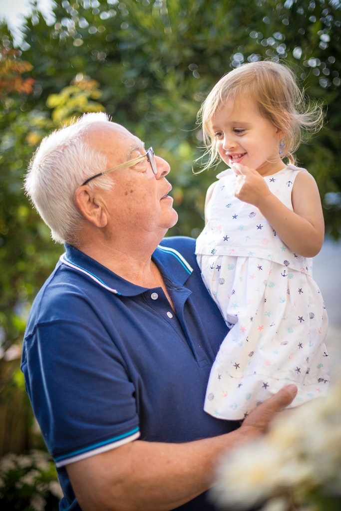 Grandfather with diabetes holding young granddaugher.