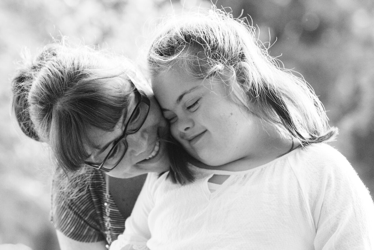 Portrait of a mother with her daughter of 12 years old with Autism and Down Syndrome in daily lives