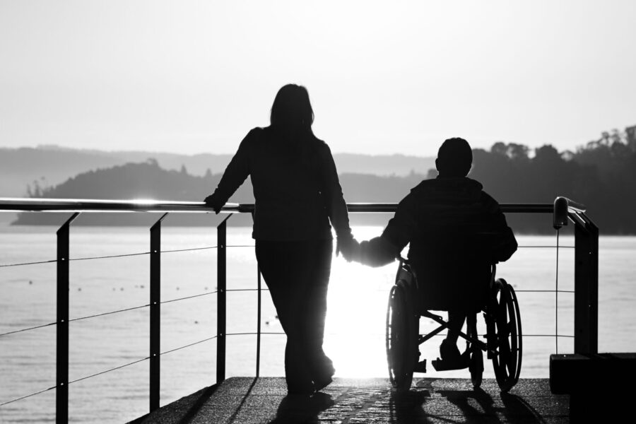 Woman and boy in wheelchair holding hands by the sea.