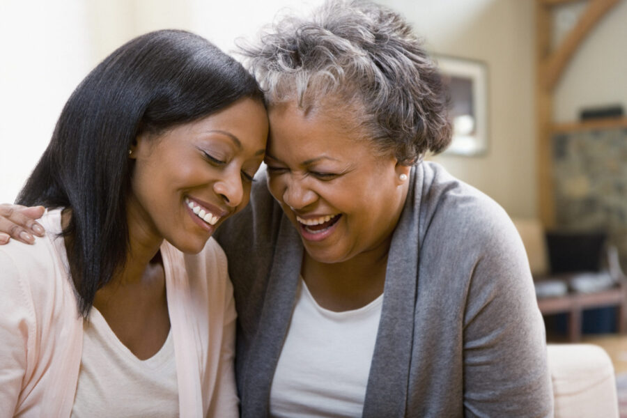 Elderly mother laughing with adult daughter