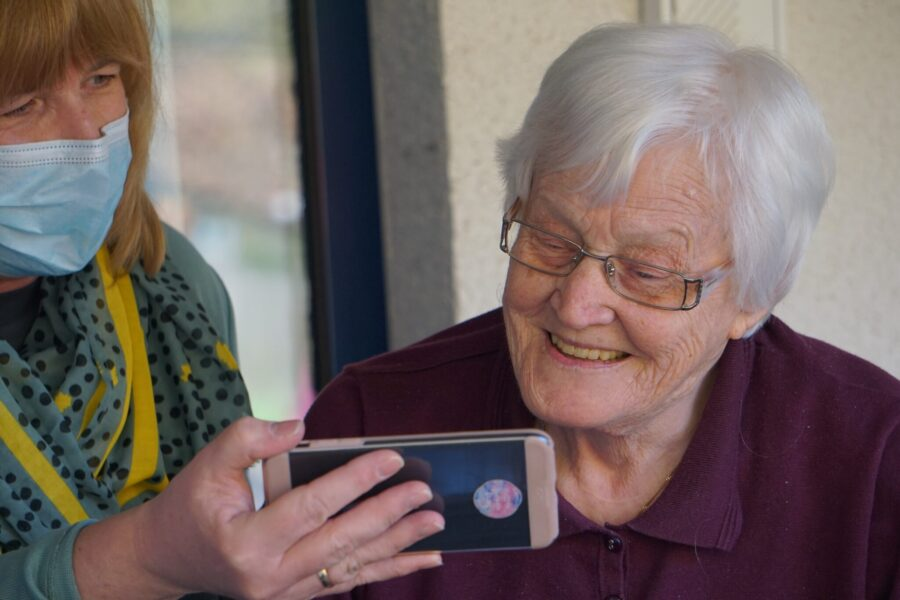 Elderly woman learning how to use smartphone with family caregiver.