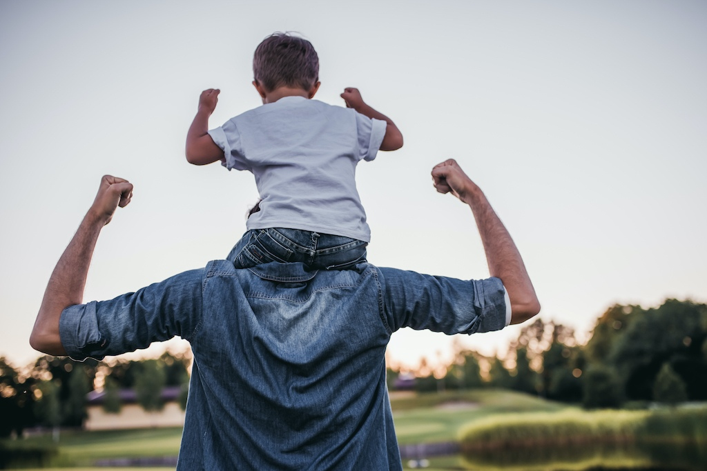 Happy father carrying young son on shoulders walking in park.