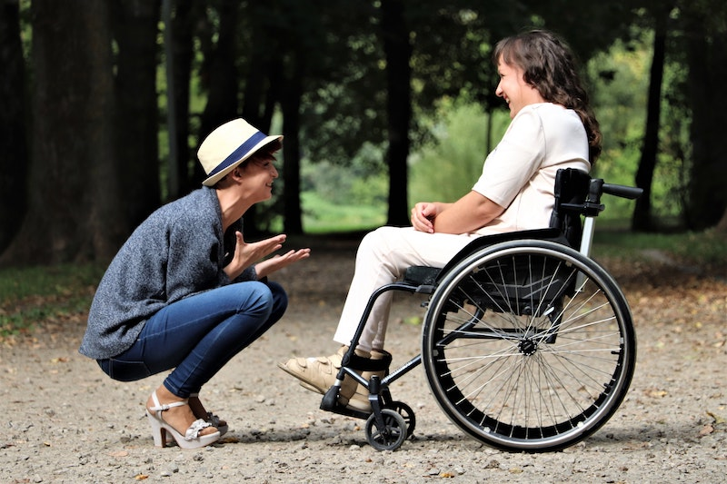 One woman in wheelchair laughing with friend.