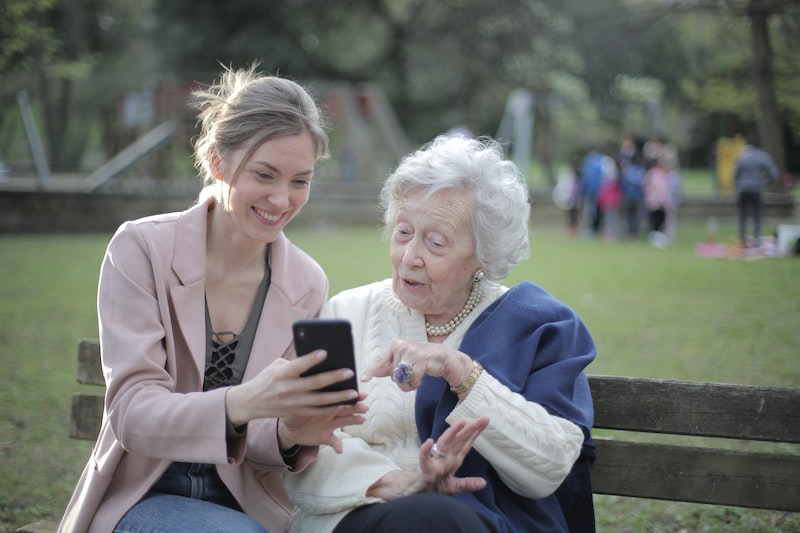 An older woman and her PCA looking at smartphone.
