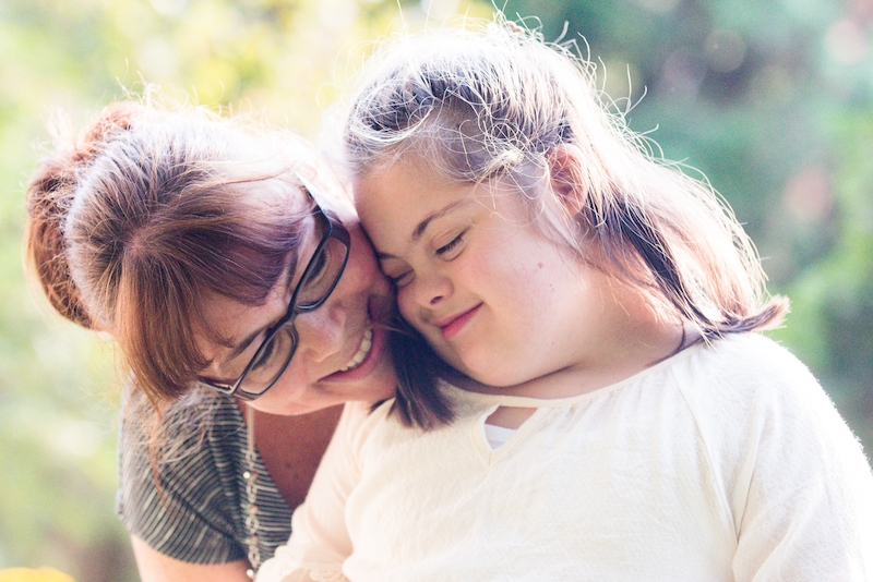 Portrait of mother with her daughter of 12 years old with Down Syndrome
