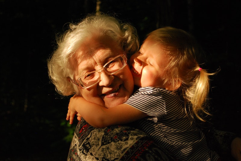 Grandmother and her young granddaughter hugging.