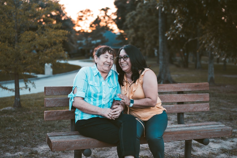Older woman sitting with adult daughter on outdoor bench.