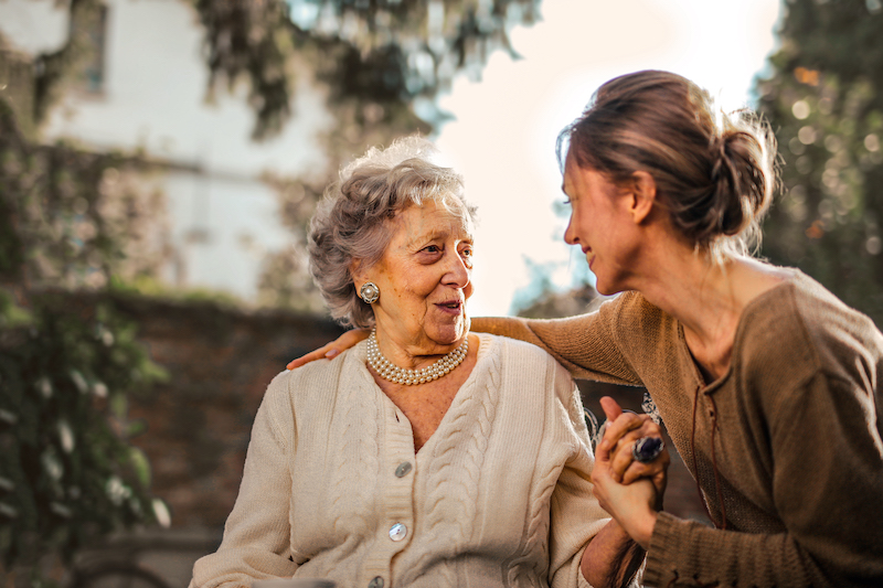 Elderly mother sitting with adult daughter smiling