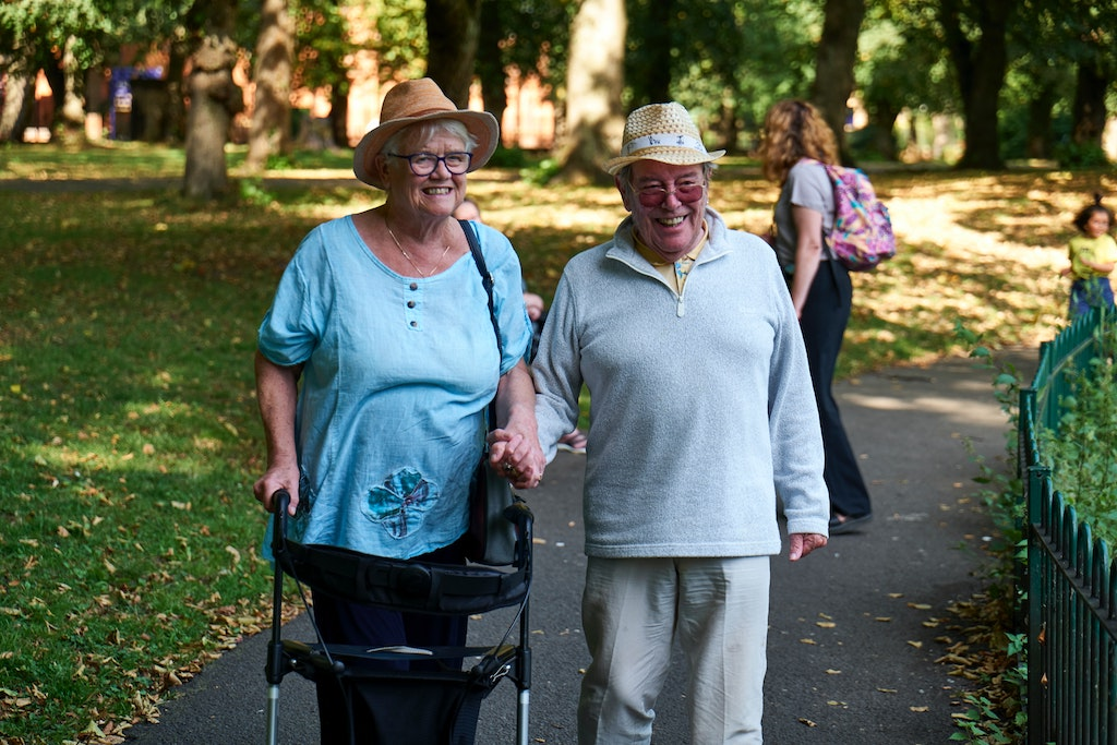 Woman walking after hip replacement with home caregiver.