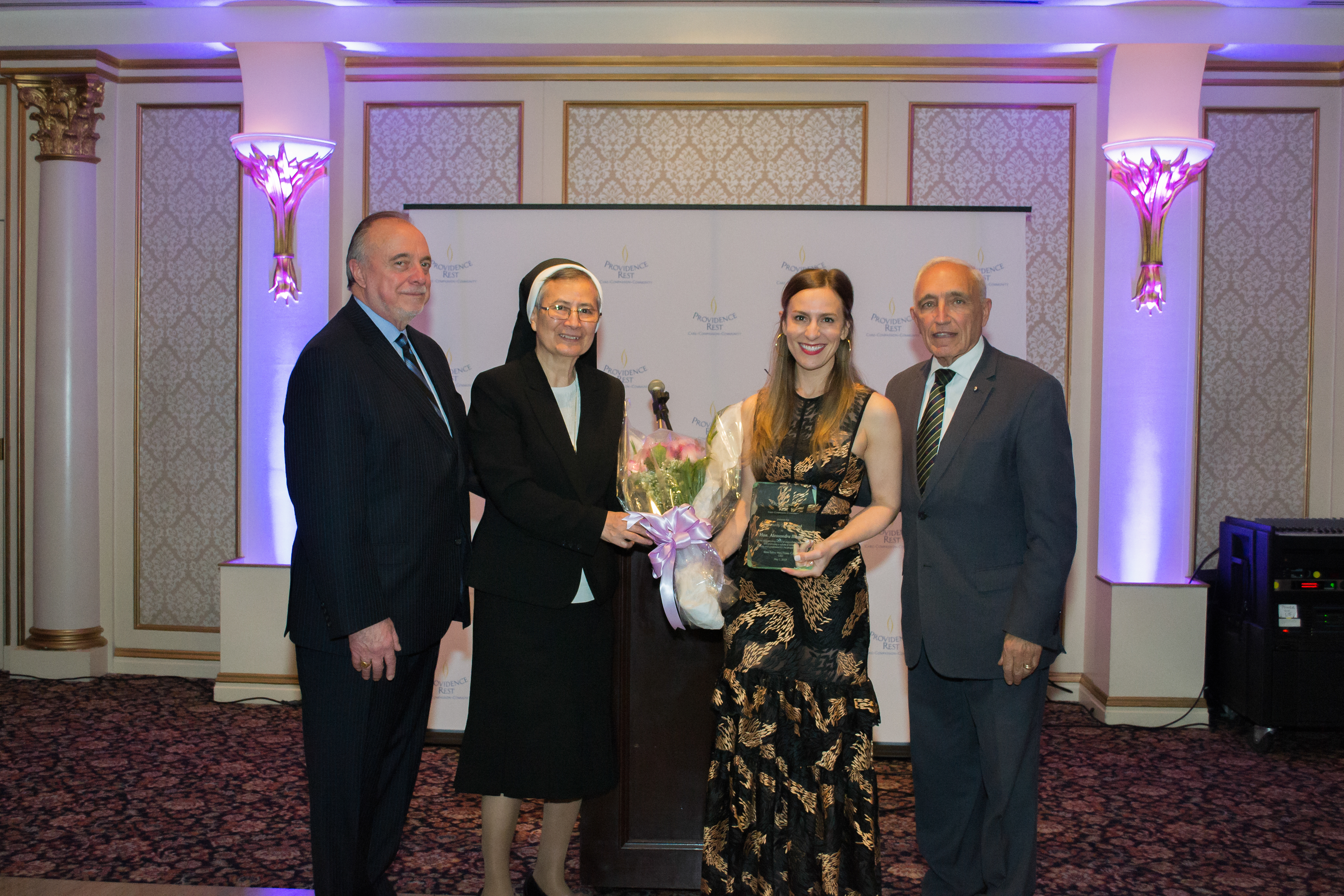 Sister Seline Mary Flores with Honoree, Alessandra Biaggi, and two male participants at the 2019 Spring Gala.