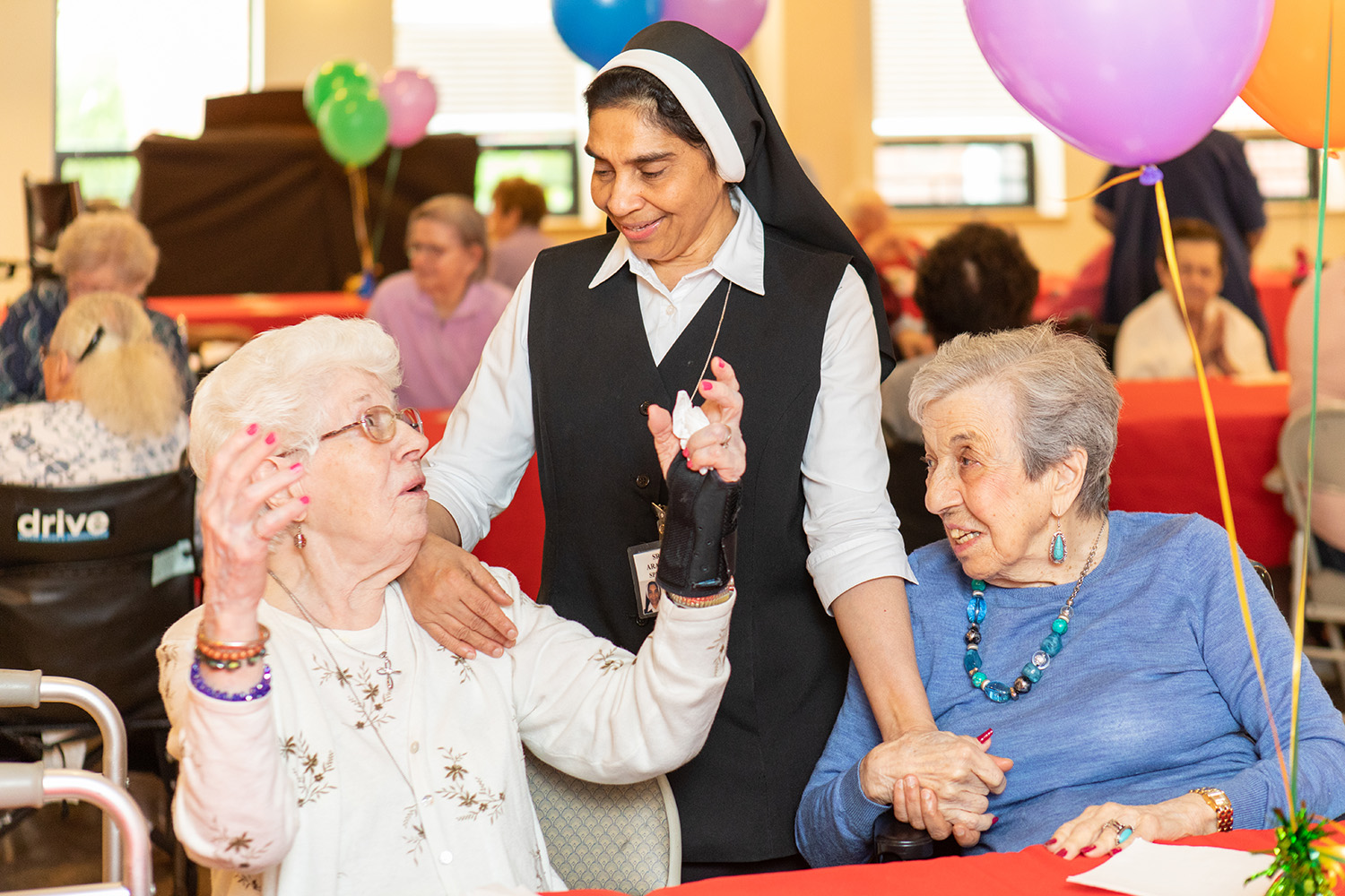 A nun holding a happy conversation with two female senior patients at a social gathering.