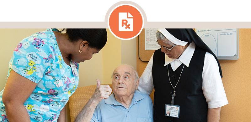 Cropped image of male senior patient giving a thumbs-up in response to being tended by female nurse and a nun on staff.