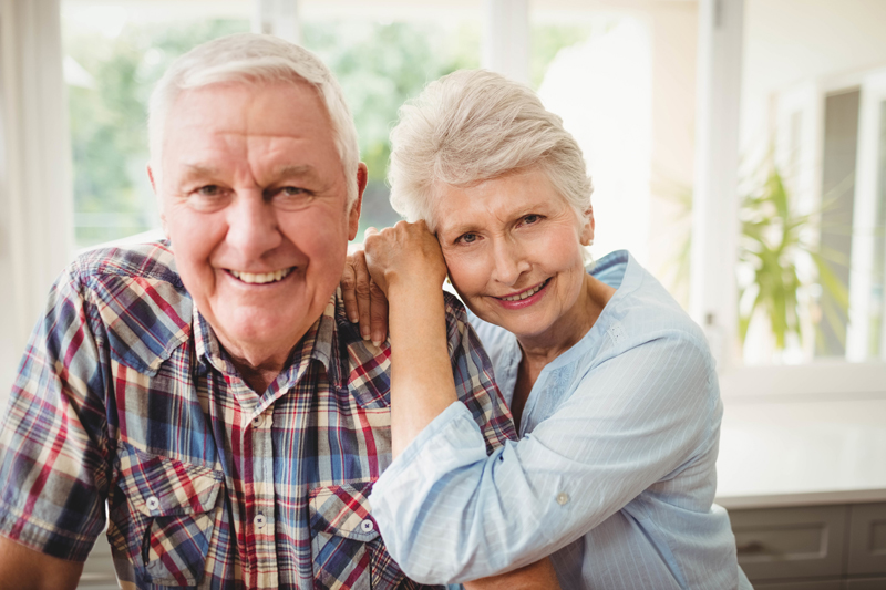 portrait-of-senior-couple-smiling-at-home-l