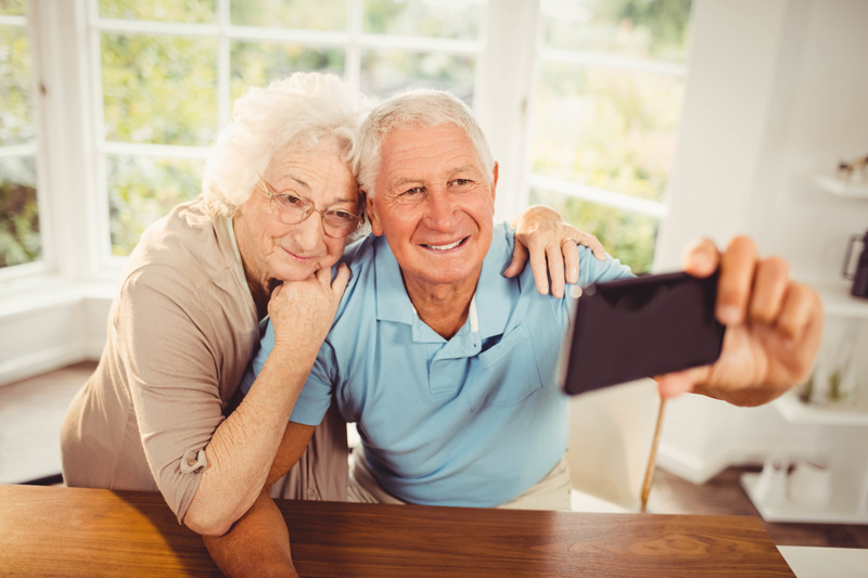 smiling-senior-couple-taking-selfie-at-home-l