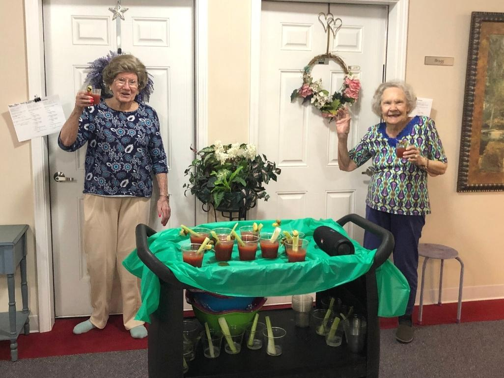 Two senior living residents enjoying bloody mary drinks that were brought to their door on a trolly for happy hour.
