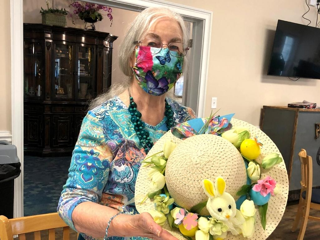 Senior resident participating in an Easter bonnet crafting session.