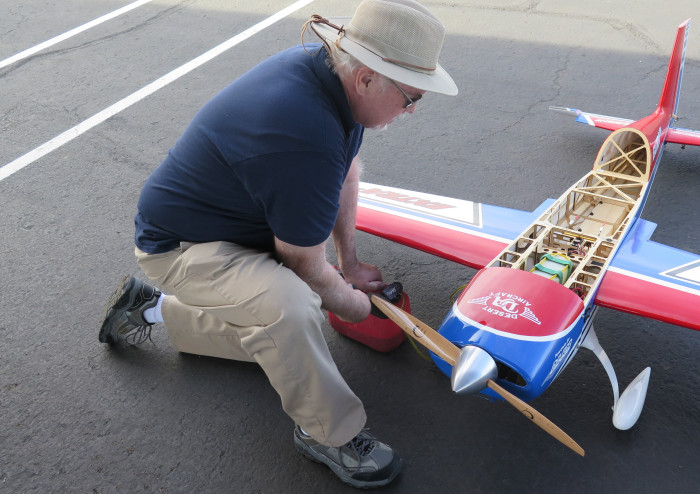 photo of Jim filling the planes fuel tank during preflight preparation.