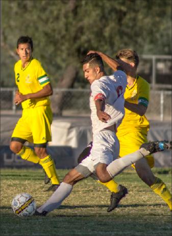 Mesa player drives the ball forward towards Yavapi's No.2 Juan Ramirez and against another Yavapai  player.