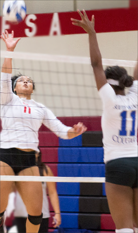 No. 11 Breanna Scott going up for a kill for the Thunderbirds as South Mountain's No. 11 Leoash Barker and No.13 Adria Herriot jump for a block.