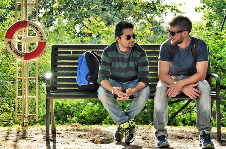 Students conversing on a bench