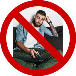 Guy on couch with TV remote covered by big, red, cross out circle