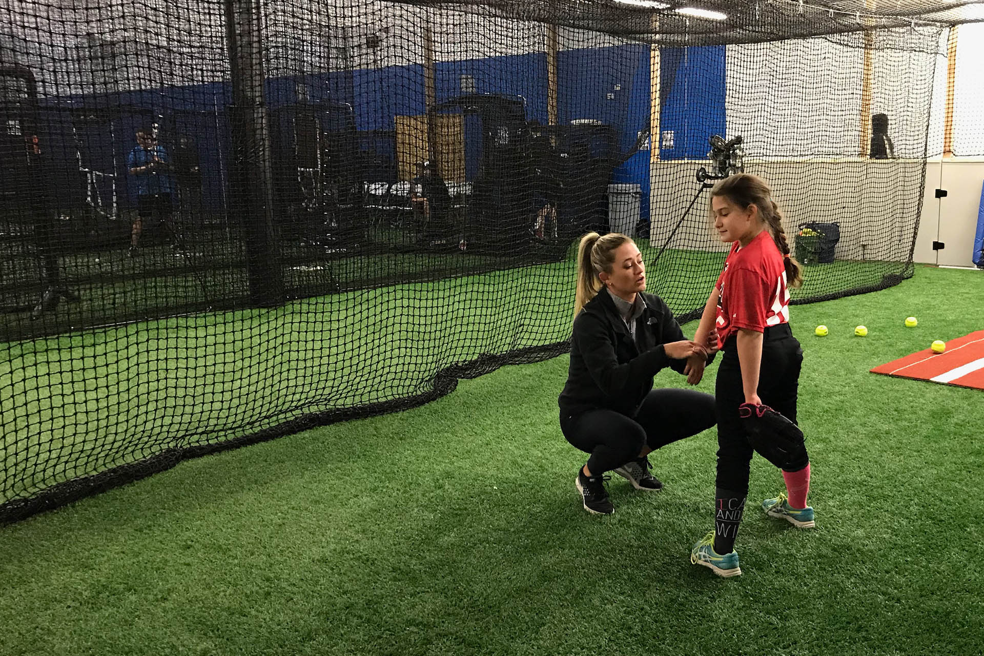 Softball pitcher teaching young girl