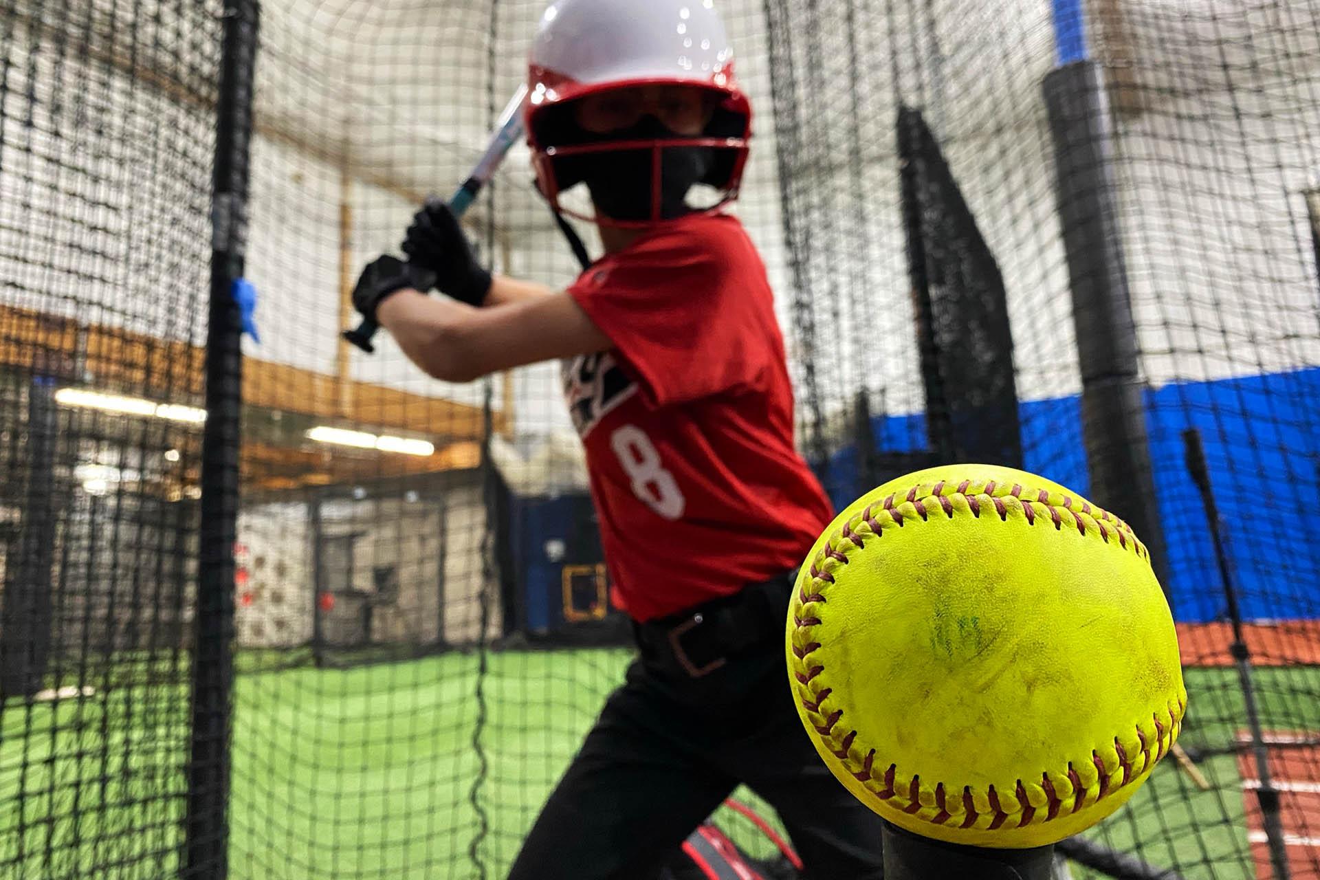 Girl Hitting a Softball Off a Tee