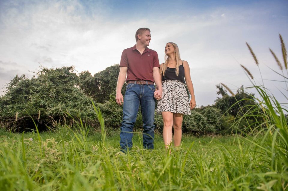 couple walking through field holding hands san antonio country rustic engagement session _7500607