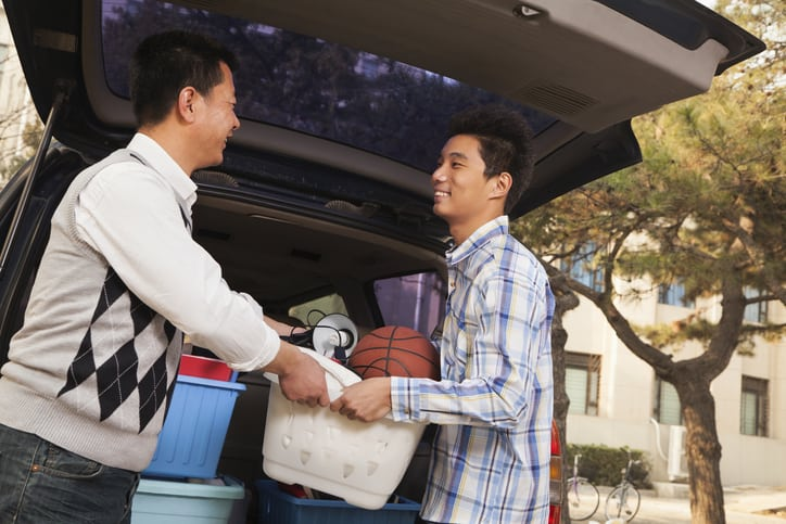 A father and son unpacking their car for college move in