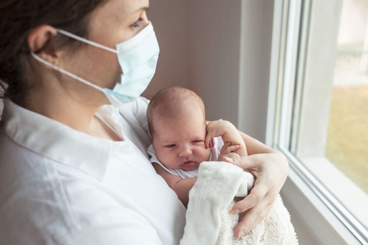 Mother with protective mask with baby