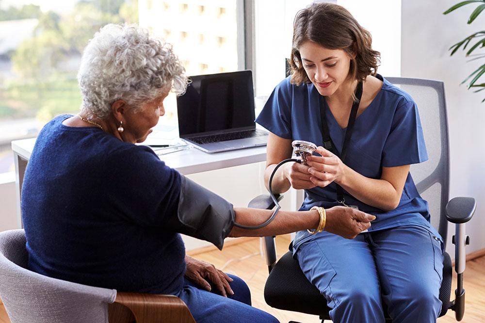 Nurse checking an elderly woman's blood pressure