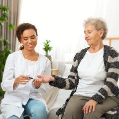 caretaker giving blood sugar test on old lady