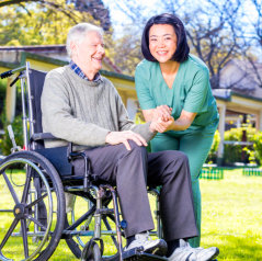 caretaker holding hand of old man in wheelchair