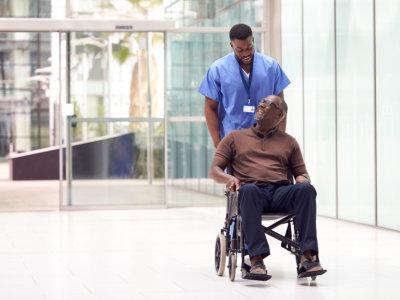 caregiver assisting elder man sitting on a wheelchair