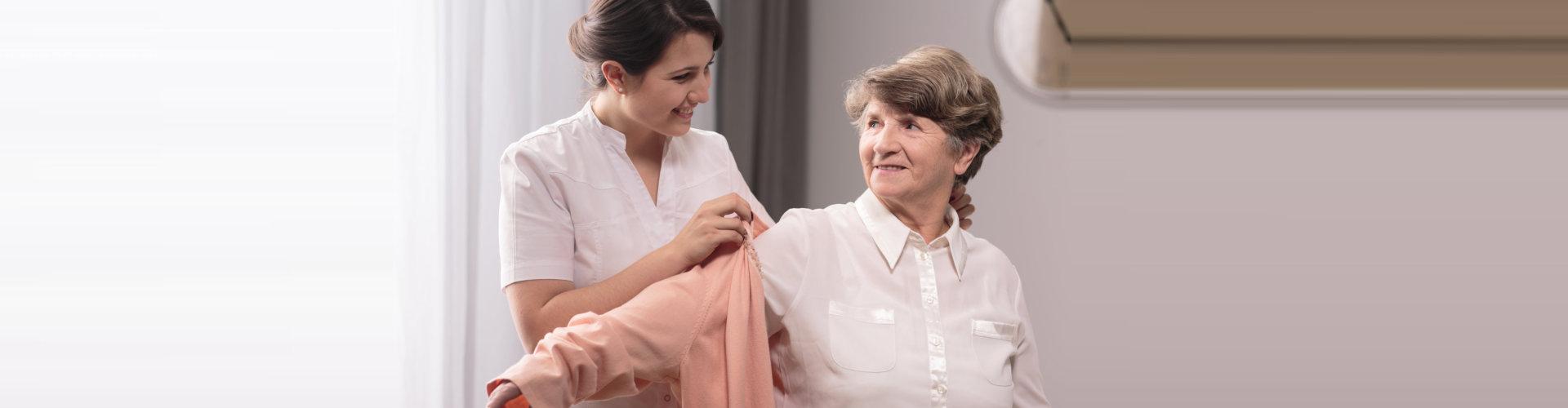 caregiver assisting elder woman on wearing a shirt