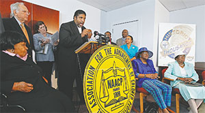 The Rev. William Barber, head of the North Carolina NAACP, at podium, announces that the group would file a lawsuit against a voter ID bill during a press conference held in Durham, N.C. on Aug. 13, 2013. Seated are plaintiffs Carolyn Q. Coleman, left, Mary Perry, second from right, and Rosanell Eaton, right. Lead attorneys Adam Stein, top left, and Penda Hair, second from top left, stand behind Barber. (CHRIS SEWARD/RALEIGH NEWS & OBSERVER/TNS)