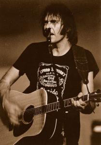 Neil Young in his Lynyrd Skynyrd whiskey shirt.