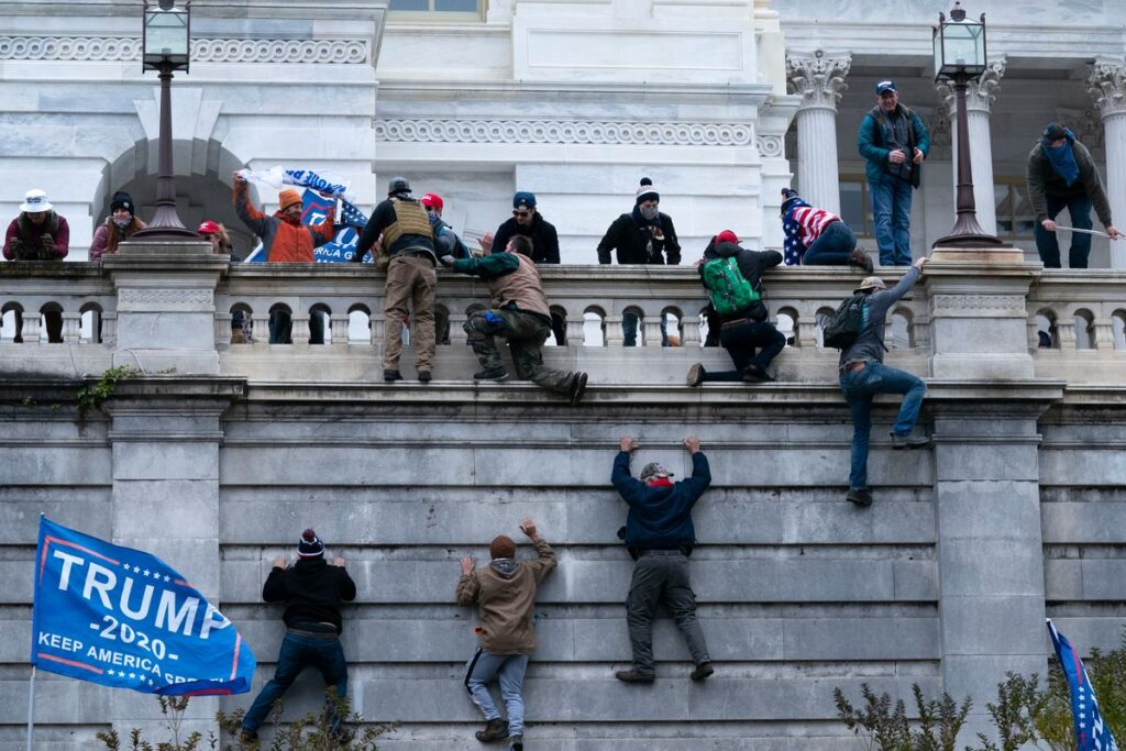 Trump's confederates scaling wall of the US Capitol.