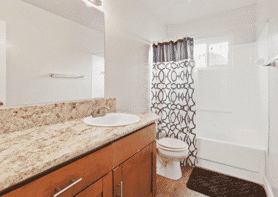 Bathroom with counter and sink with door to toilet and shower/bathtub
