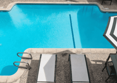 Pool with poolside recliners and umbrella